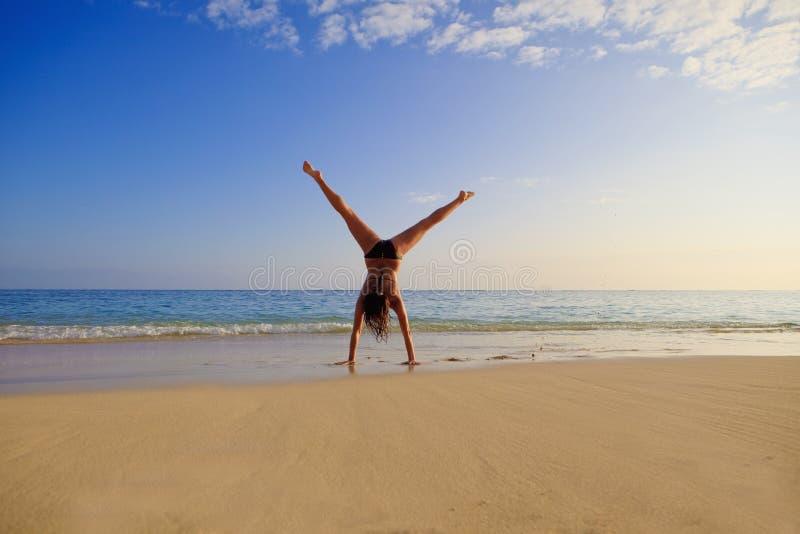 Giovane donna che fa un cartwhee fotografia stock