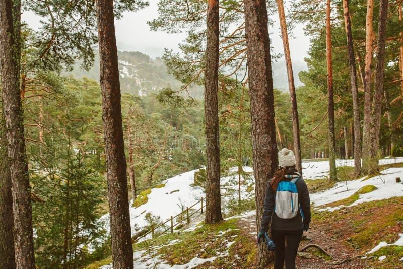 Giovane donna che fa un'escursione nel concetto bianco di stile di vita della foresta di inverno fotografia stock libera da diritti