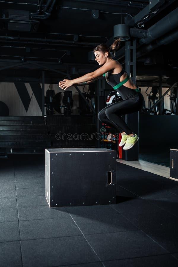 Giovane donna che fa un esercizio di salto della scatola fotografia stock