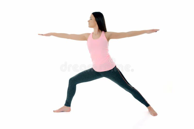 Giovane donna che fa yoga,  Virabhadrasana di posa del guerriero immagini stock libere da diritti