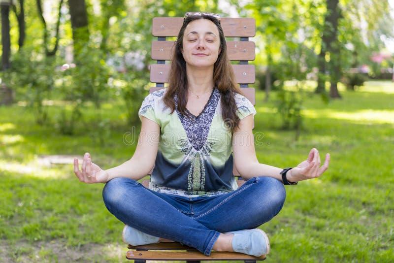 Giovane donna che fa yoga nel parco sul banco Ritratto di bella giovane donna castana calma che si rilassa e che fa esercizio di  fotografie stock