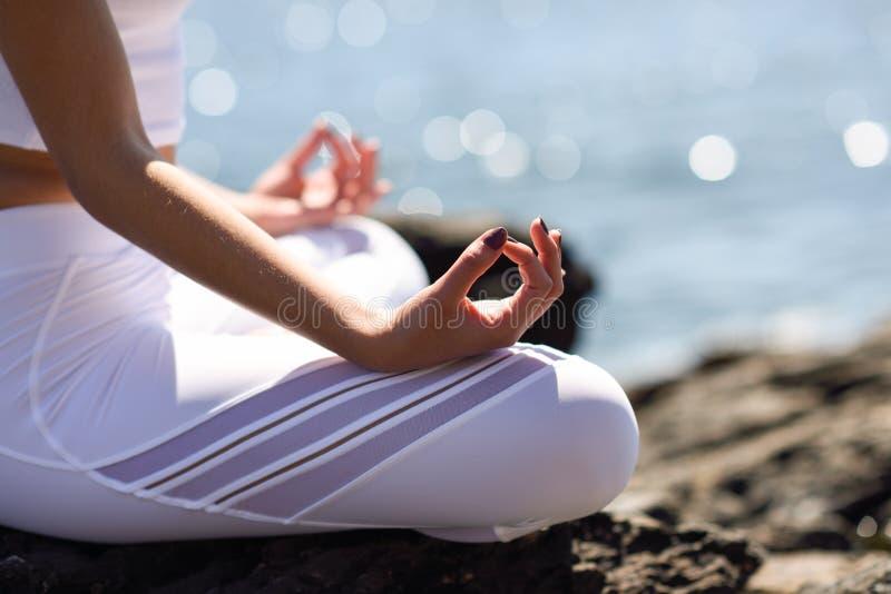 Giovane donna che fa yoga nella spiaggia fotografia stock libera da diritti