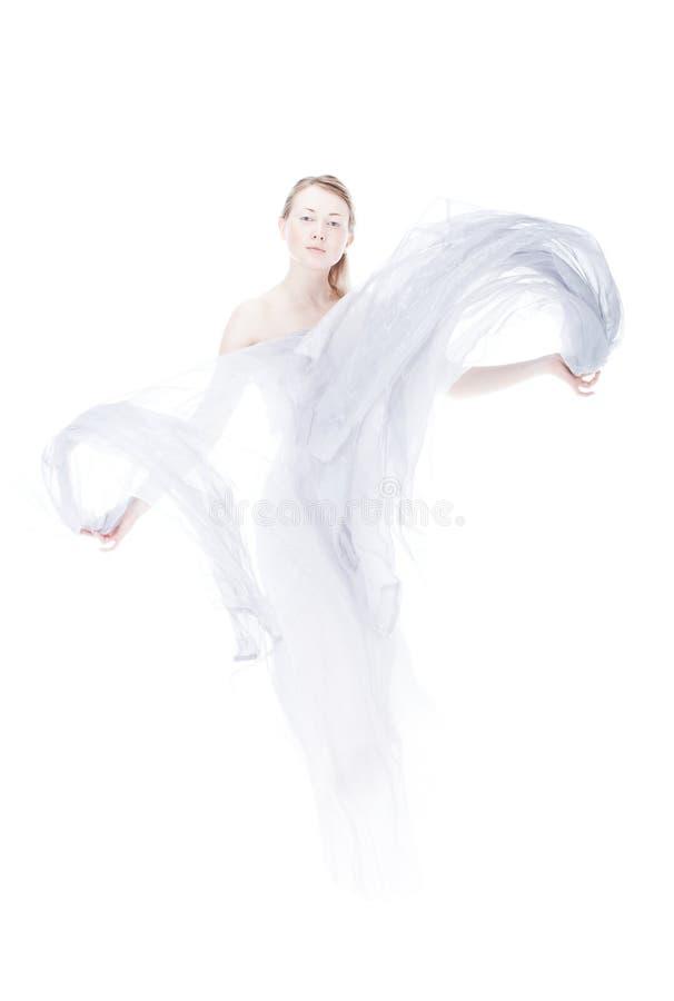 Giovane donna che fluttua dal tessuto chiaro immagini stock