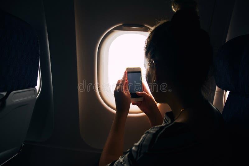 Giovane donna che fotografa vista dalla finestra degli aerei durante il volo nell'aeroplano fotografia stock libera da diritti