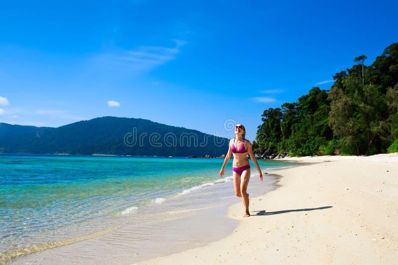 Giovane donna che funziona lungo la spiaggia fotografia stock