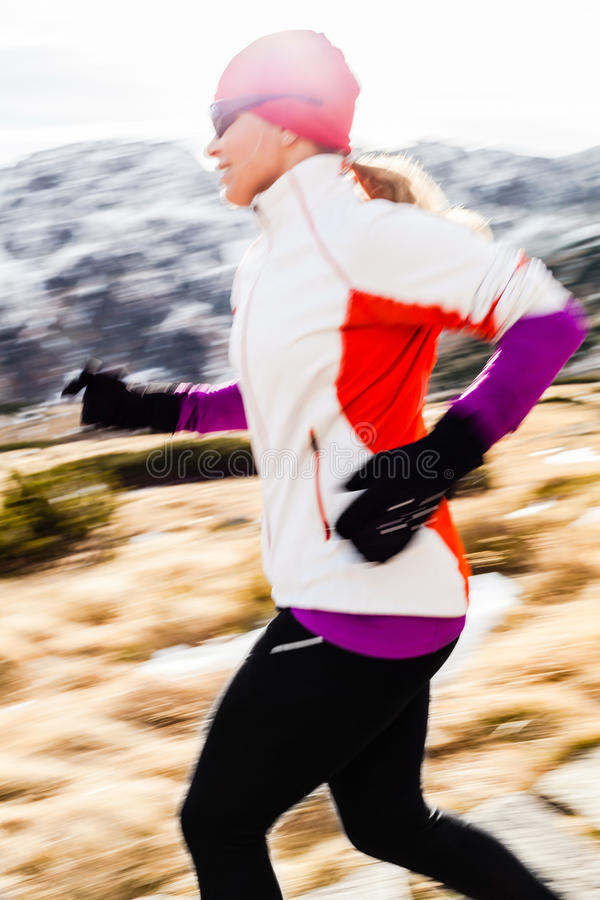 Giovane donna che funziona in montagne sulla caduta di inverno immagini stock libere da diritti