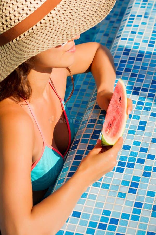 Giovane donna che galleggia nello stagno blu immagini stock
