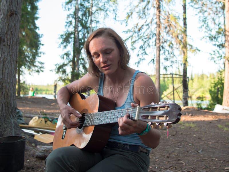 Giovane donna che gioca chitarra immagine stock