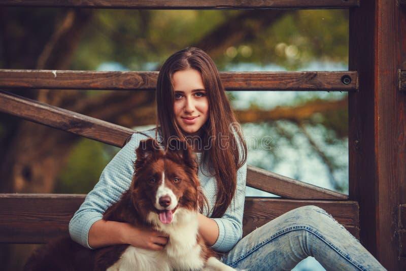 Giovane donna che gioca con il cane delle collie fotografia stock libera da diritti