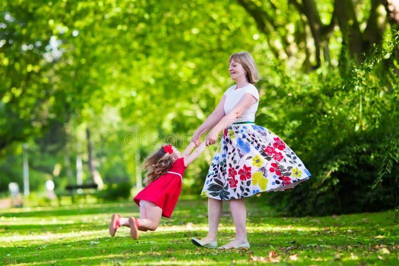 Giovane donna che gioca con la bambina in un parco immagini stock