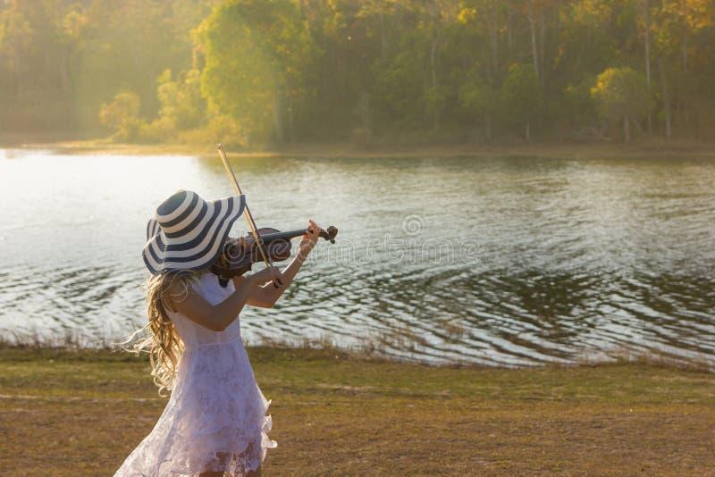 Giovane donna che gioca il violino sul fondo della natura immagini stock