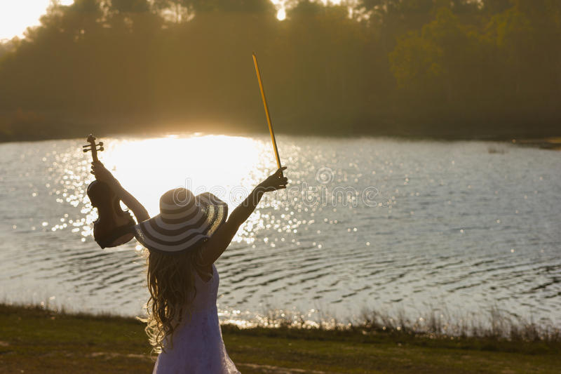 Giovane donna che gioca il violino sul fondo della natura fotografia stock libera da diritti