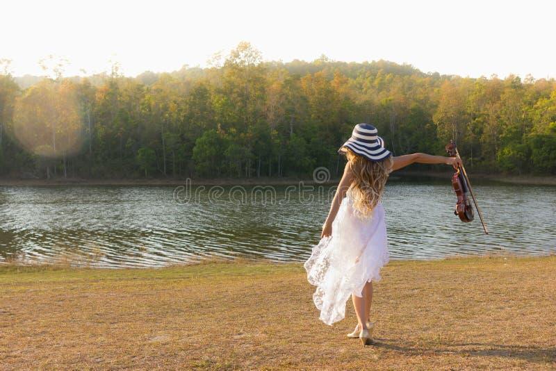 Giovane donna che gioca il violino sul fondo della natura fotografia stock