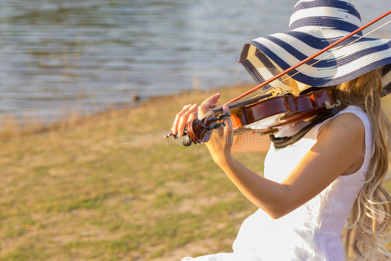 Giovane donna che gioca il violino sul fondo della natura fotografie stock