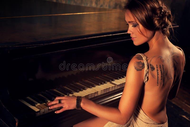 Giovane donna che gioca piano fotografie stock libere da diritti