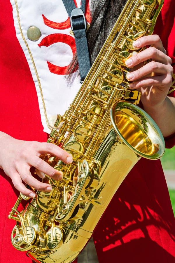 Giovane donna che gioca sassofono tenore nell'orchestra di jazz fotografia stock