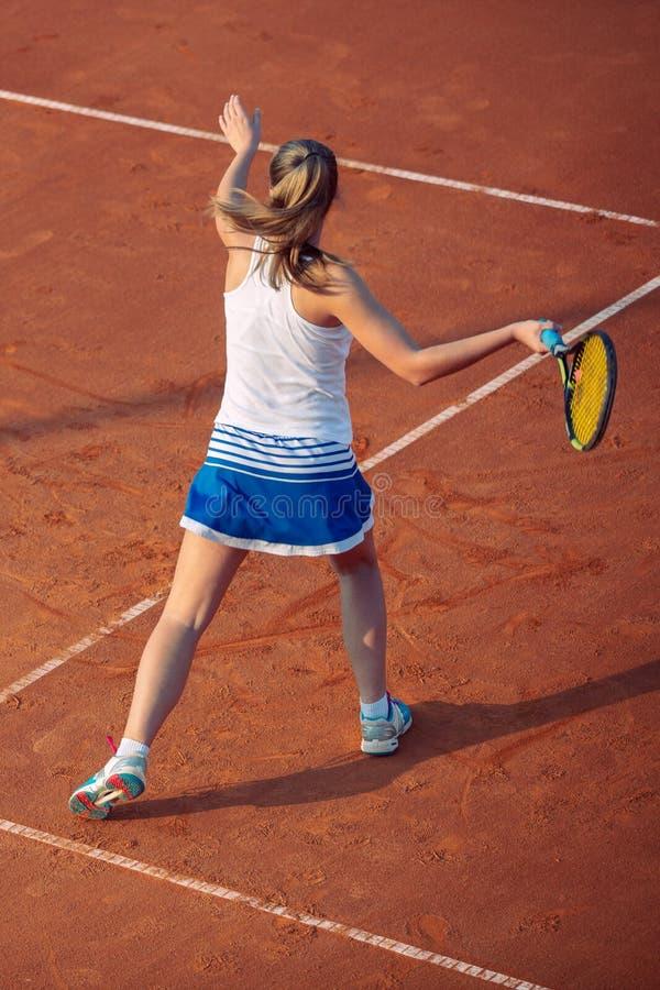 Giovane donna che gioca a tennis sull'argilla forehand fotografia stock libera da diritti