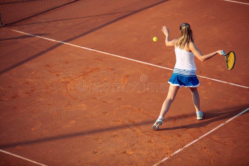 Giovane donna che gioca a tennis sull'argilla forehand immagini stock libere da diritti