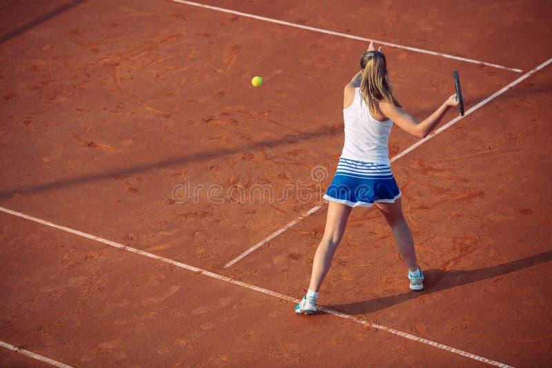 Giovane donna che gioca a tennis sull'argilla forehand fotografie stock libere da diritti