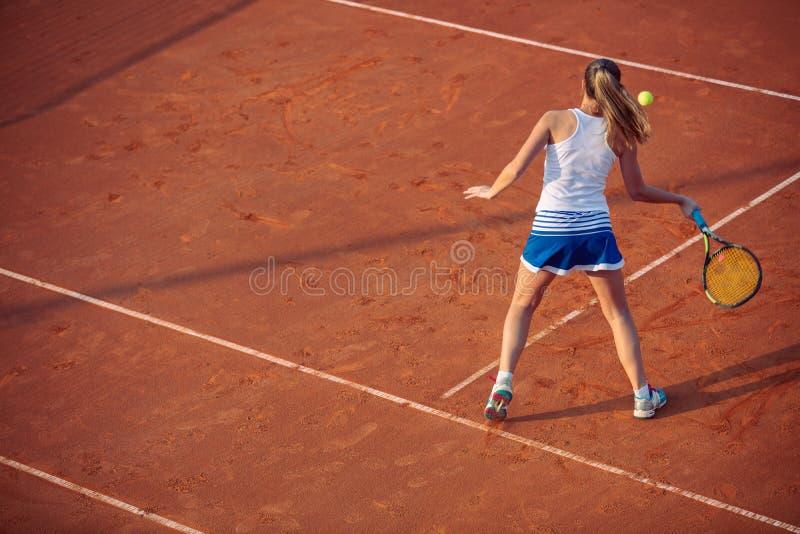 Giovane donna che gioca a tennis sull'argilla forehand fotografie stock