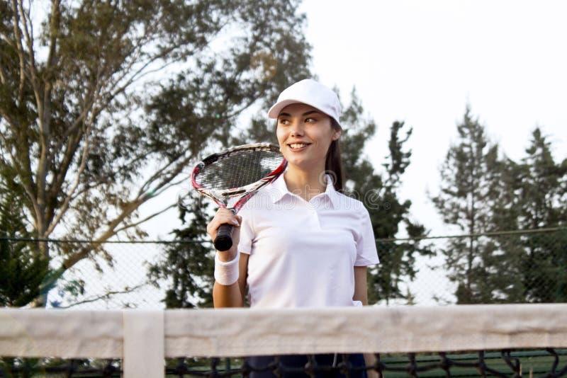Giovane donna che gioca a tennis sulla corte fotografia stock