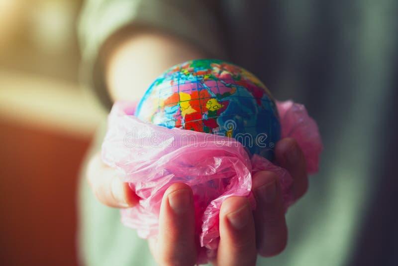 Giovane donna che giudica il globo della terra avvolto nel sacchetto di plastica fotografia stock libera da diritti