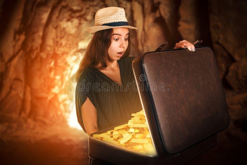 Giovane donna che giudica una valigia piena delle barre di oro immagini stock