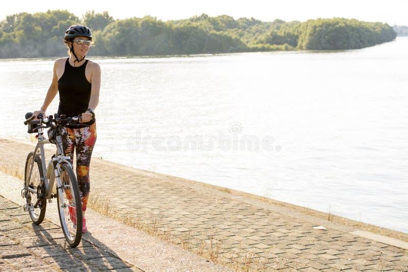 Giovane donna che gode del ciclismo vicino al fiume immagini stock libere da diritti