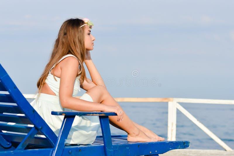 Giovane donna che gode del giorno soleggiato sui precedenti della spiaggia di estate all'aperto immagine stock