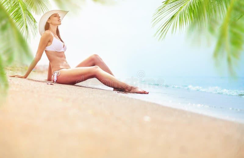 Giovane donna che gode del giorno soleggiato sulla spiaggia tropicale fotografia stock