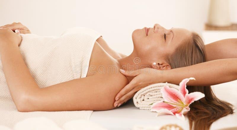 Giovane donna che gode del massaggio del collo fotografia stock libera da diritti