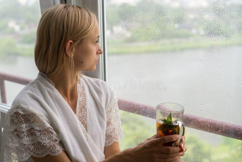 Giovane donna che gode del suo tè di mattina, guardante fuori la finestra piovosa Bello bere irriconoscibile romantico della raga immagini stock libere da diritti