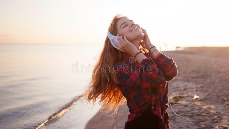 Giovane donna che gode della musica, sera meravigliosa sulla spiaggia immagini stock libere da diritti