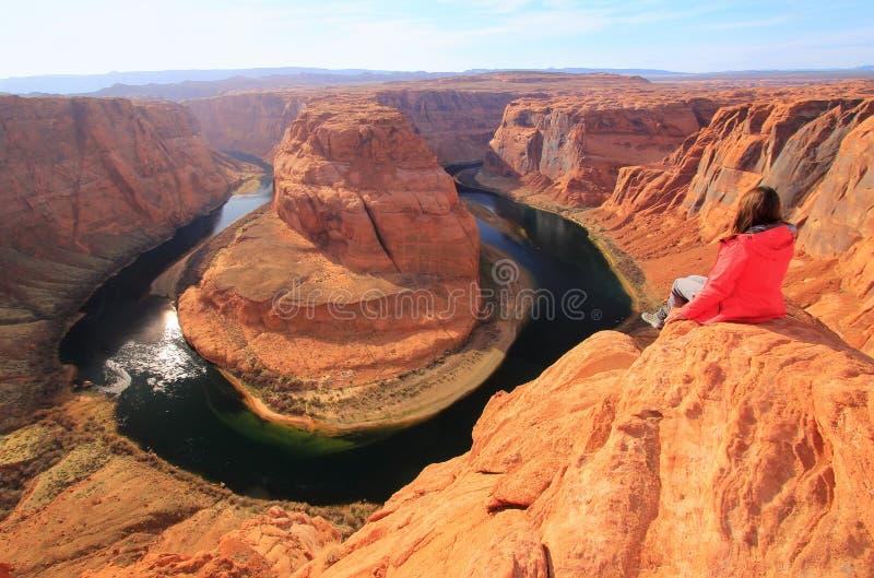 Giovane donna che gode della vista della curvatura a ferro di cavallo, Arizona, U.S.A. immagine stock
