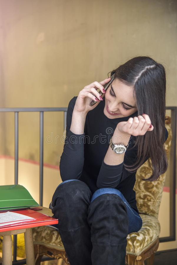 Giovane donna che gode di una tazza di caffè e che parla sul suo telefono fotografia stock libera da diritti