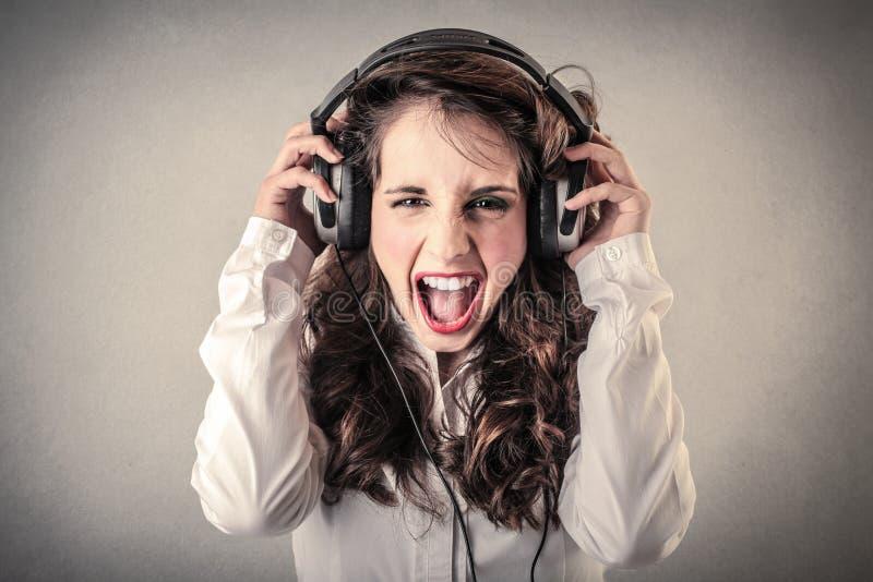 Giovane donna che grida e che ascolta la musica immagini stock