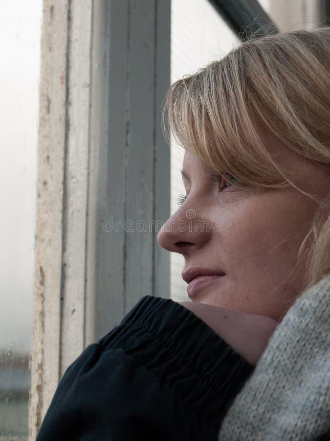 Giovane donna che guarda da una finestra fotografia stock