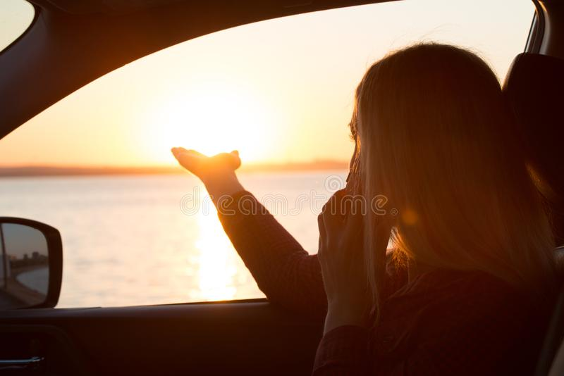Giovane donna che guarda fuori la finestra di automobile del tramonto sul mare e che parla sul telefono fotografia stock libera da diritti