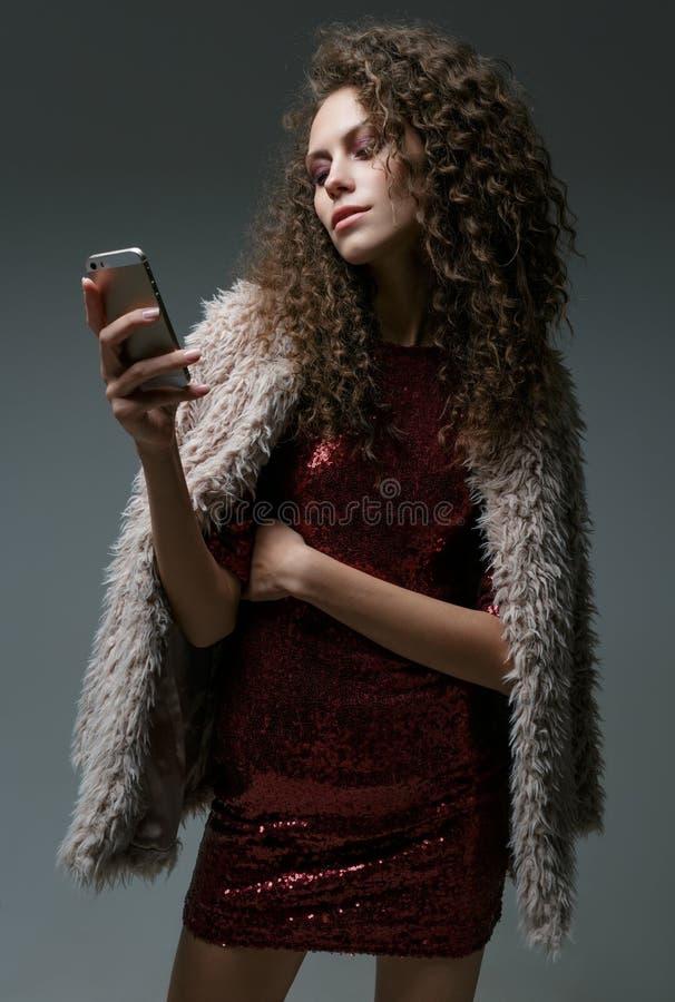 Giovane donna che guarda in suo telefono, in studio immagine stock