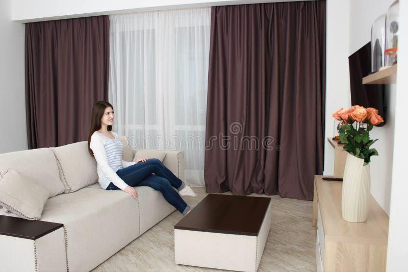 Giovane donna che guarda TV sul sofà in salone facendo uso del telecomando fotografia stock libera da diritti