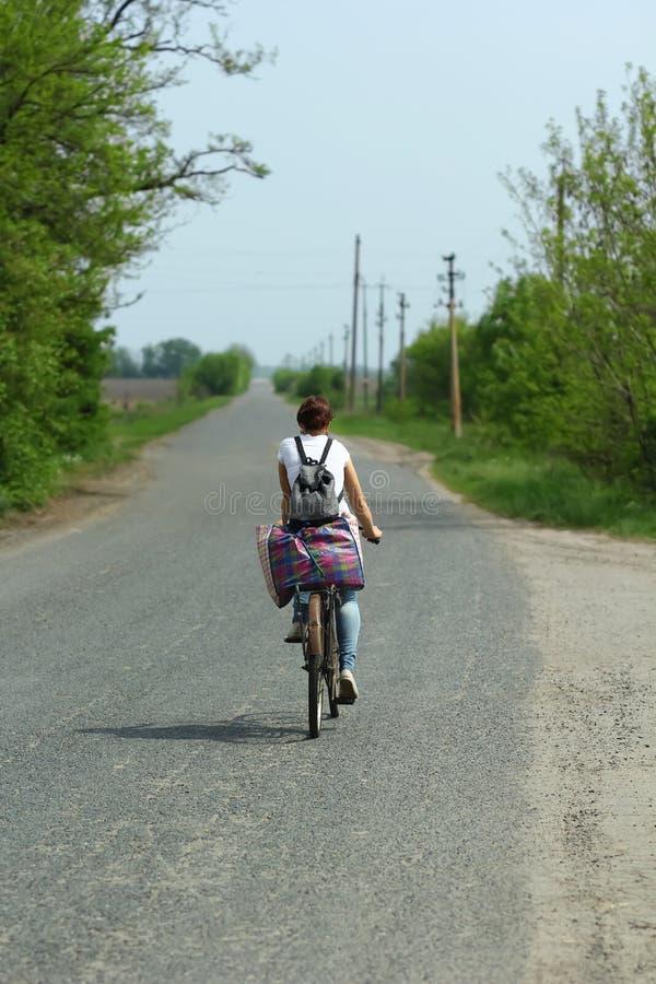 Giovane donna che guida bicicletta arrugginita lungo la strada della campagna fotografia stock libera da diritti