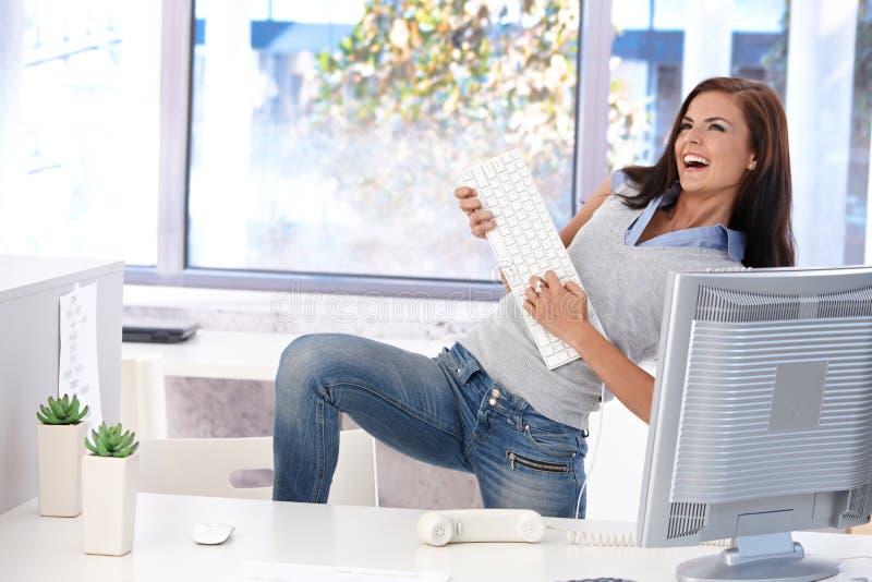 Giovane donna che ha divertimento in ufficio luminoso immagini stock libere da diritti