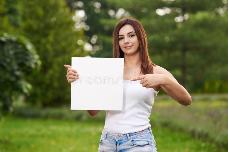 Giovane donna che indica al segno immagine stock
