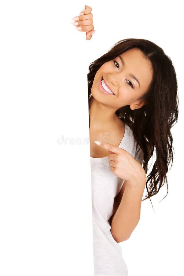 Giovane donna che indica sul bordo in bianco fotografia stock libera da diritti