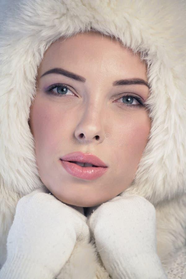 Giovane donna che indossa un cappuccio bianco della pelliccia fotografie stock