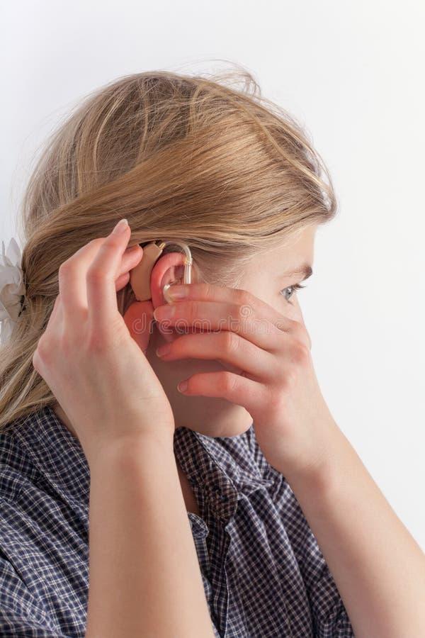 Giovane donna che inserisce una protesi acustica immagine stock libera da diritti