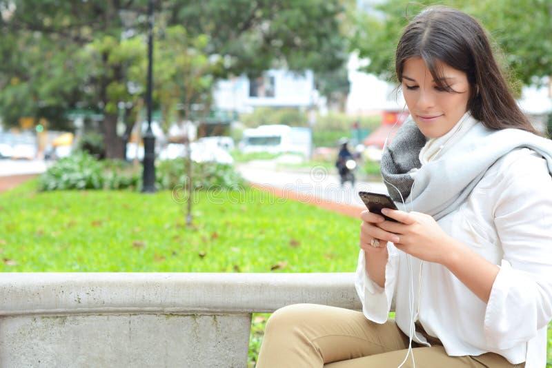 Giovane donna che invia messaggio con lo smartphone immagine stock