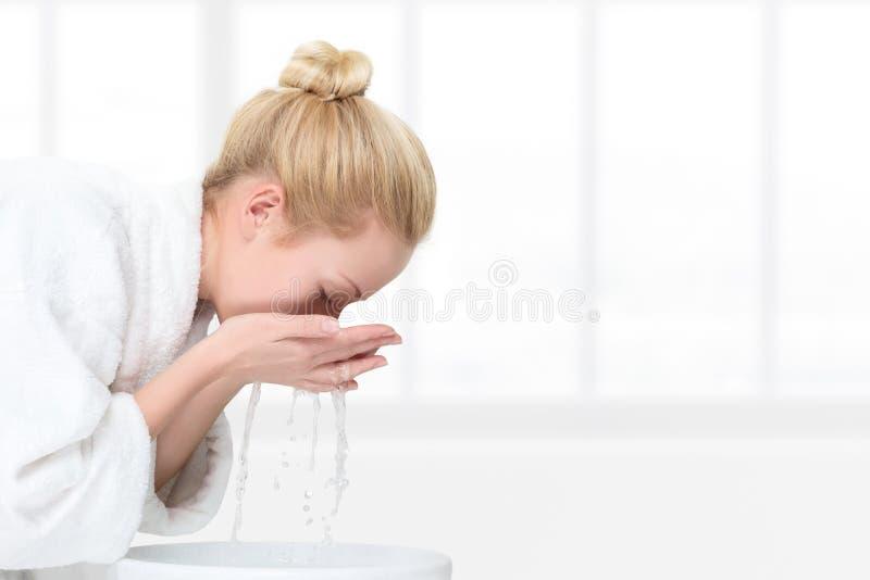 Giovane donna che lava il suo fronte fotografia stock