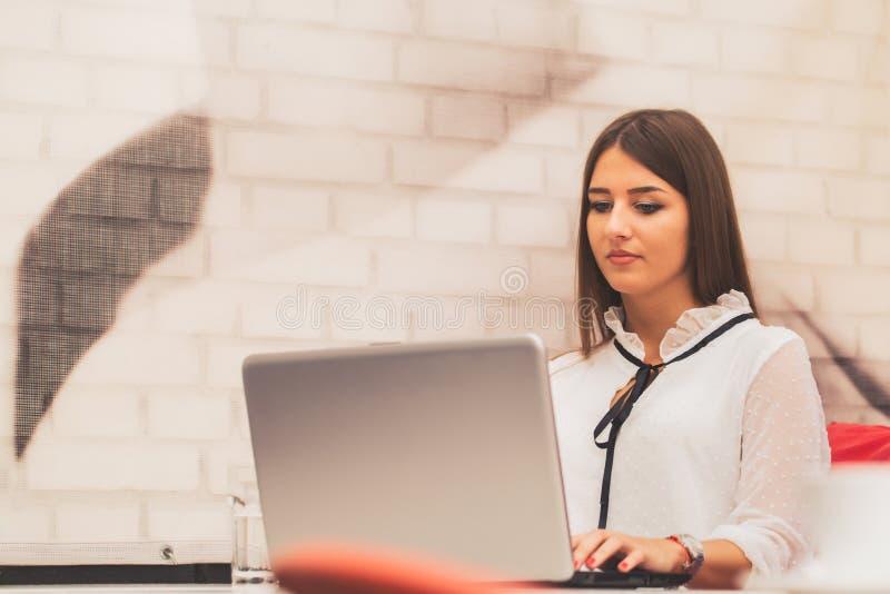 Giovane donna che lavora ad un computer portatile in una caffetteria immagini stock