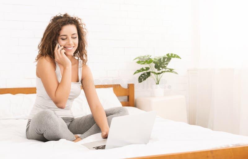 Giovane donna che lavora al computer portatile e che parla sul telefono a letto immagini stock libere da diritti